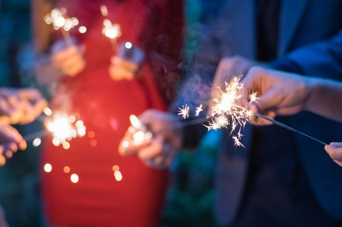 Young people holding fireworks at a party.