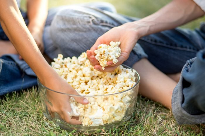 Family eat popcorn in park or backyards, detail