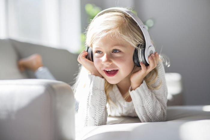 A Happy little girl listening music lying on the sofa living-room