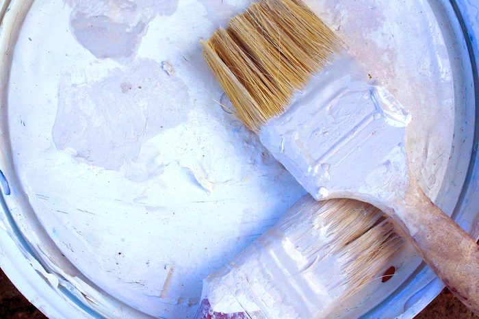 Dirty white painted soaked short two wooden brushes placing on color bucket round plastic lid cover, with space frame background