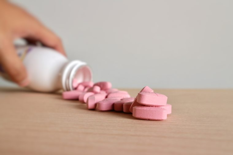 Hand hold medicine bottle and focus pink pills on wood table