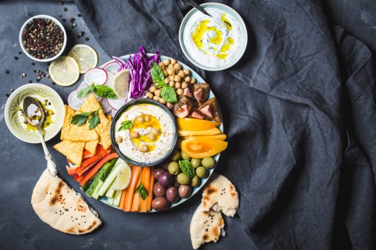 Meze platter with hummus, yoghurt dip, assorted snacks. Space for text. Hummus, vegetables sticks, chickpeas, olives, pita, chips. Plate, Middle Eastern/Mediterranean meze. Party/finger food. Top view