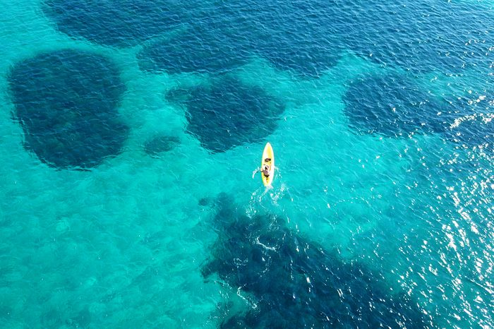 Aerial drone bird's eye view of kayak cruising in tropical rocky seascape with turquoise and sapphire clear waters