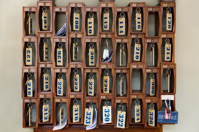 Hotel keys with room numbers hanging at reception desk counter