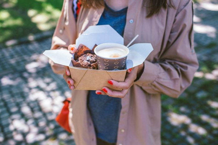 in the hands of the girl a box with fresh coffee and a cupcake, takeaway food concept