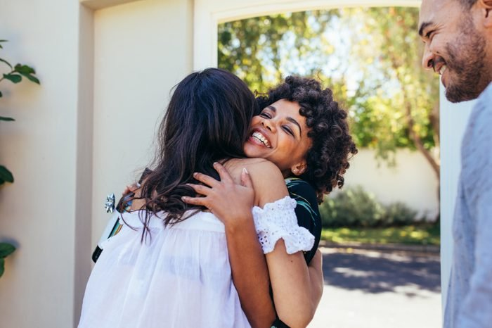 African woman greeting female friend for having a new house. Smiling young woman congratulating her friend. Couple welcoming friend for housewarming party.