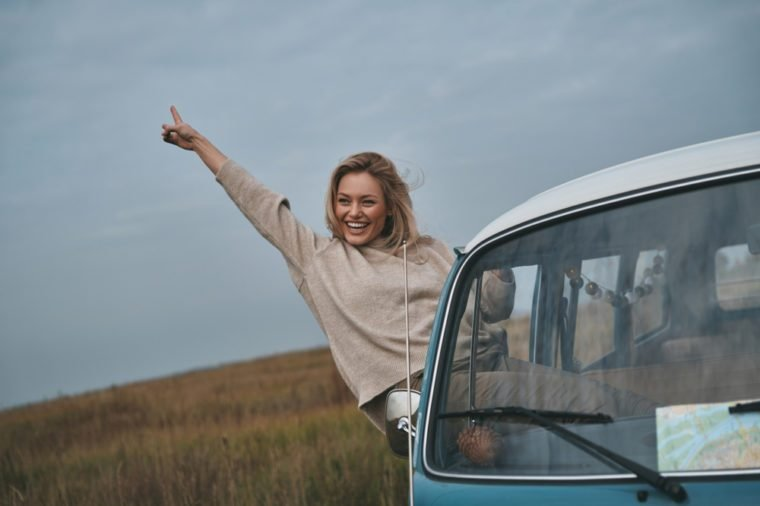 Life is awesome! Attractive young smiling woman leaning out the van?s window and gesturing while enjoying the car travel