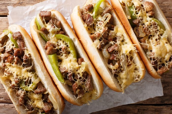 Philadelphia cheesesteak sandwich close-up on paper on the table. Horizontal top view from above