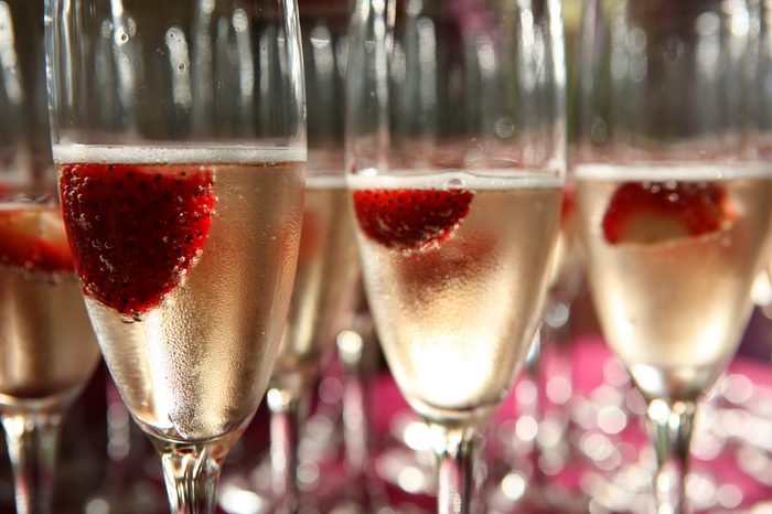 Champagne glass with strawberries inside close up with many other glasses