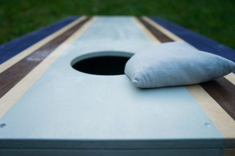 Cornhole bean bag toss wood game board outside on grass