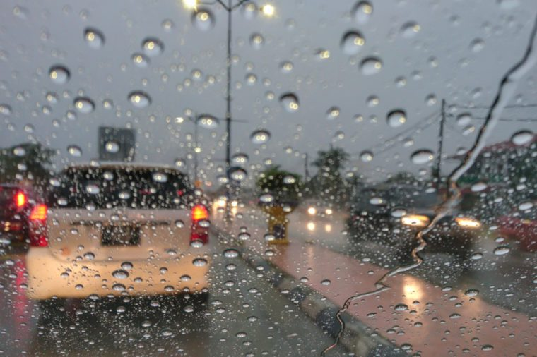 Road view through car window with rain drops driving in rain.Traffic view from car windscreen in rain.Driving in rain.Selective focus