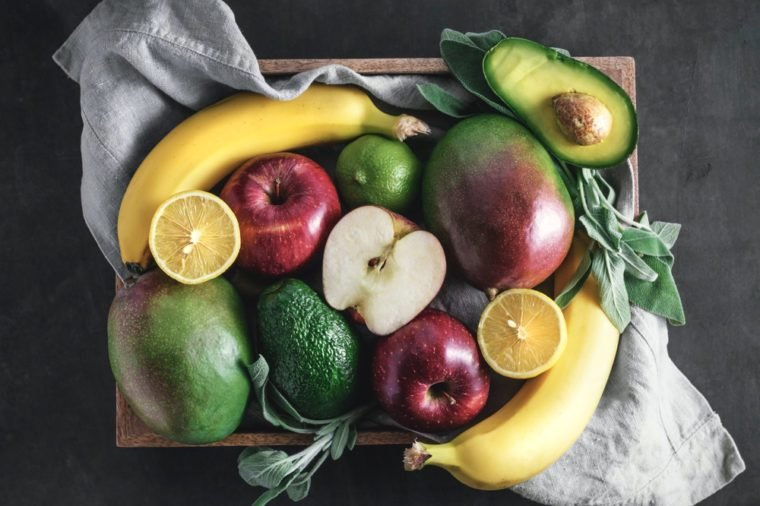 Top view of fresh fruits in the wooden box on black.