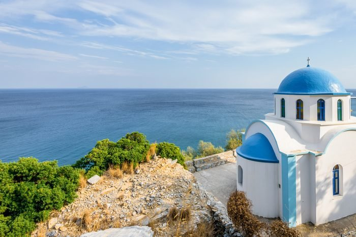 Holy white blue greek church shining over Ikaria island at the mediterranean sea sourrounded by beautiful landscape and magical bays, Ikaria, Greece