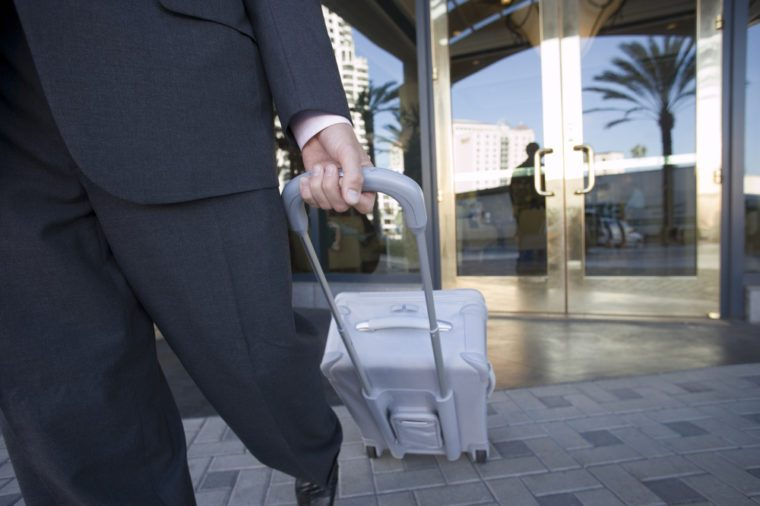Businessman leaving hotel with luggage, mid-section, front view