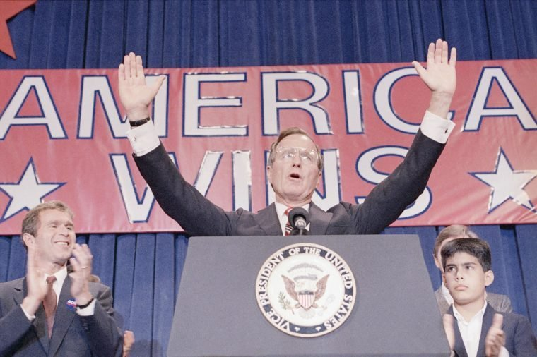 President-elect George H. W. Bush holds his hands up to acknowledge the crowds applause, and ask them to allow him to continue his speech, during his victory rally with grandson, George P. Bush, right, and son George W. Bush, left, Houston, Texas