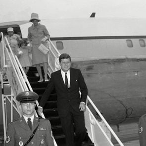 John Kennedy, JFK, Jacqueline Kennedy President John F. Kennedy leaves his plane at Otis Air Force Base, Mass.,, for a long weekend holiday at his nearby Hyannis Port home. Mrs. Jacqueline Kennedy walks down the ramp hand-in-hand with daughter Caroline. Nurse Maud Shaw carries John Jr., in the background