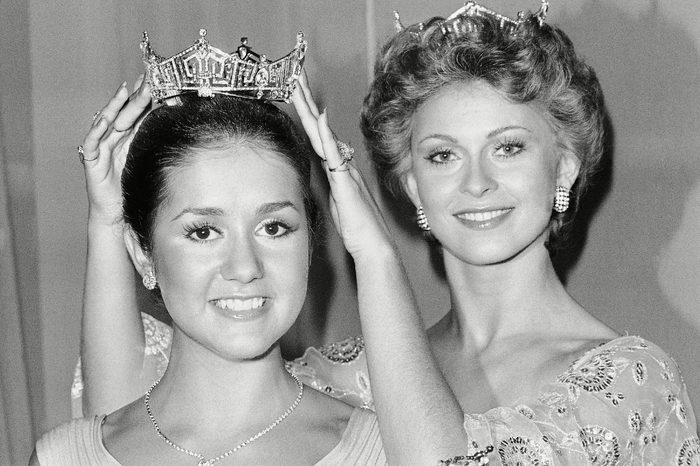 Miss America 1976, Tawny Elaine Godin of Saratoga Springs, New York, left, is crowned by Miss American 1975 Shirley Cothran, right, at the pageant in Atlantic City, N.J