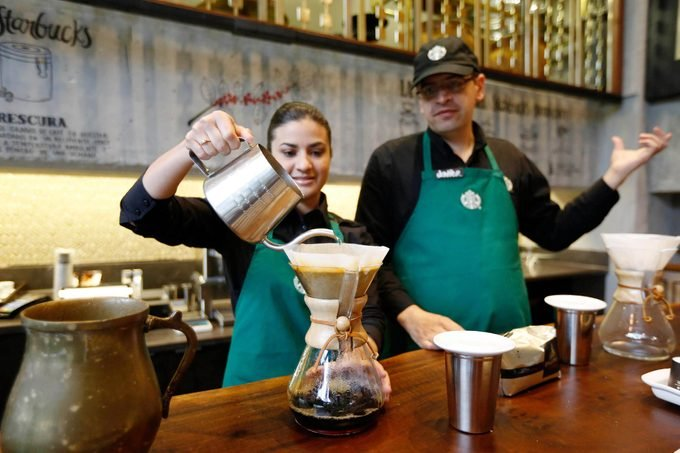 A Starbucks employee demonstrates the preparation of a cup of coffee during a media tour of the new shop in Bogota, Colombia, . The three-floor coffee house in Bogota is the first of 50 that the Seattle-based company plans to open here in the next five years