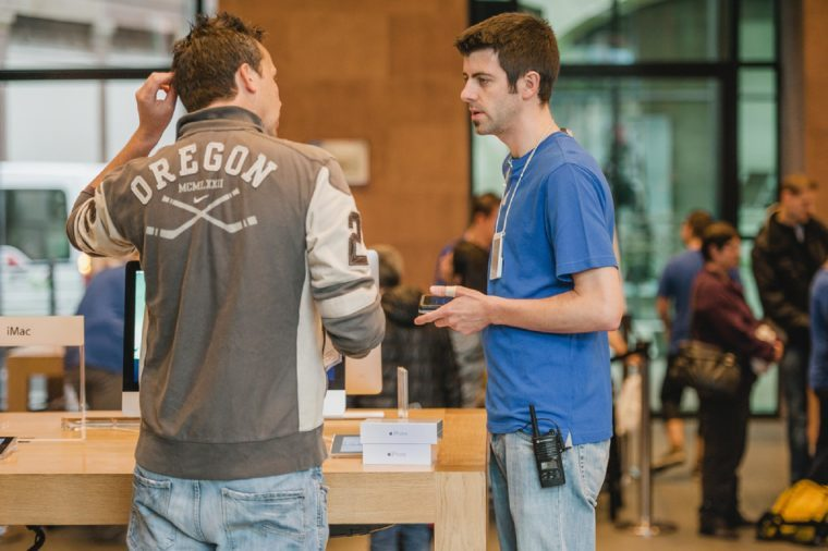 STRASBOURG, FRANCE - SEPTEMBER 19, 2014: An Apple Inc. genius employee assists a customer with the purchase during the sales launch of the iPhone 6 and iPhone 6 Plus
