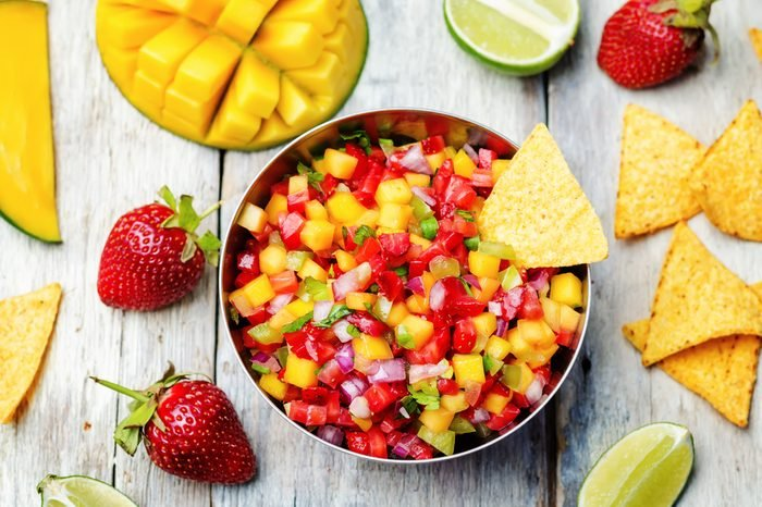 strawberry mango pepper salsa on a white wood background. toning. selective focus