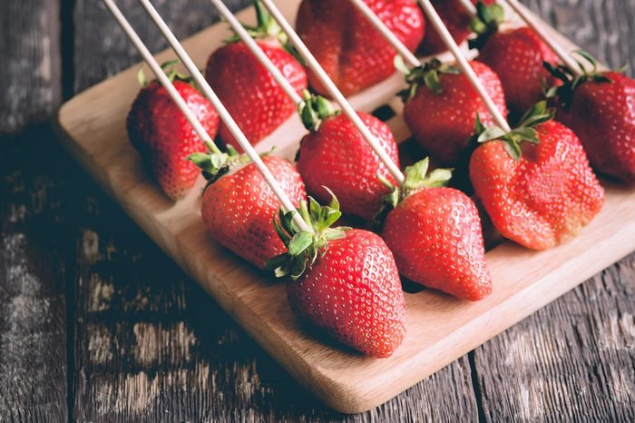 Strawberries on skewers are lying on wooden board Wooden background Filtered