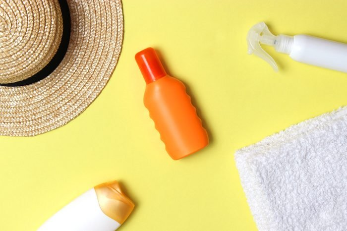sunscreen, towel, hat, glasses on a colored background. Cosmetics for prevention of sunburn.top view, flatlay