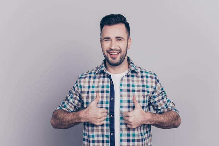 Portrait of smiling, bearded, perfect man showing two thumbs up in checkered shirt over grey background