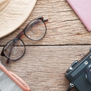 Creative flat lay of eyeglasses, hat, bag, camera and passport on wooden texture background, Travel vacation concept