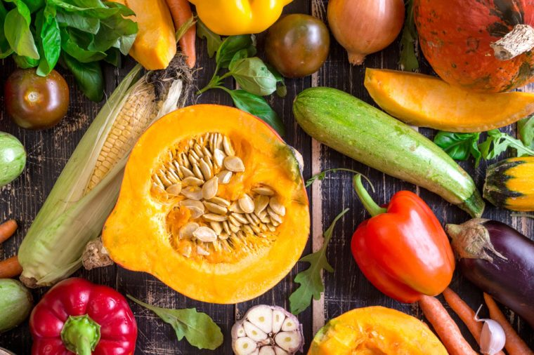 Close up of fresh vegetables on a rustic dark table. Autumn background. Healthy eating. Sliced pumpkin, zucchini, squash, bell peppers, carrots, onions, cut garlic, tomatoes, eggplant. Top view