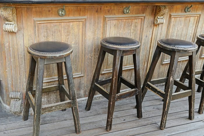 Vintage and rustic wooden bar stools on wooden floor in front of wooden bar with handbag hook hanger