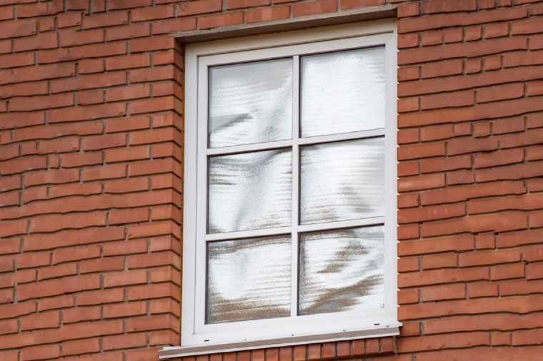 Foil in the window of red brick private house to reflect the summer sun