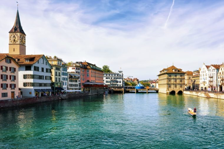 Zurich, Switzerland - September 2, 2016: Man in a boat at Limmat River quay and St Peter Church in the city center of Zurich, Switzerland