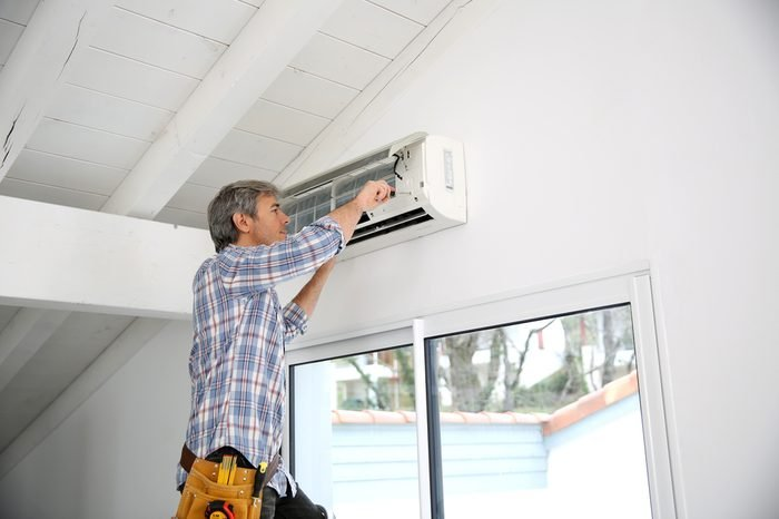 Repairman fixing air conditioner unit