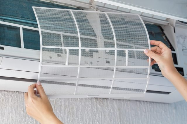 Dirty filter of air conditioner in female hands. Cleaning and washing maintenance