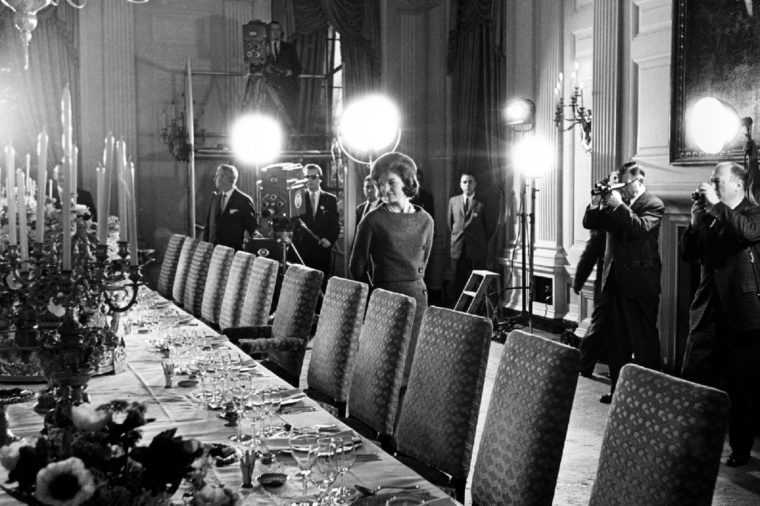 Jacqueline Kennedy U.S. first lady Jacqueline Kennedy, center, checks the table setting of the White House gold service in the state dining room as she conducts a tour of the newly-restored White House for television cameras in Washington to be aired the month afterwards. More than 80 million Americans tuned in