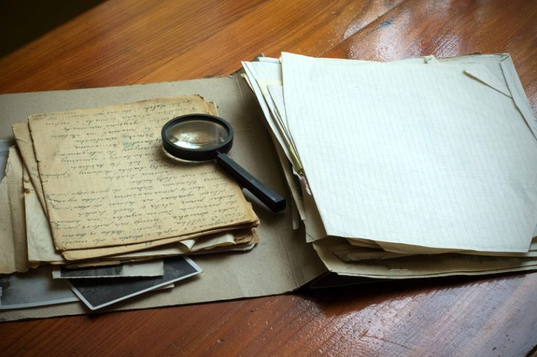 Vintage documents with magnifying glass investigation concept