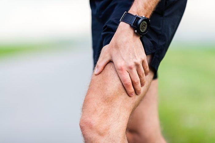 Runner leg and muscle pain during running training outdoors in summer nature. Health and fitness concept. Injured male jogger massage sore leg.