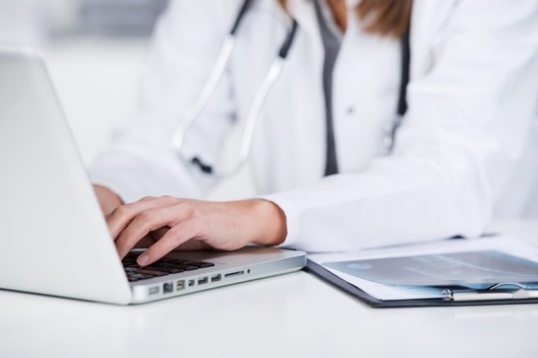 Midsection of female doctor using laptop at desk