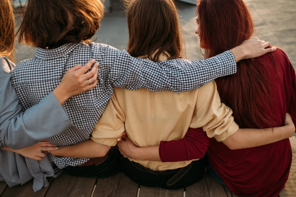 Pastime collaboration lifestyle teenage. Back view of young diverse people group. Arm around. Unity support. Friendship togetherness