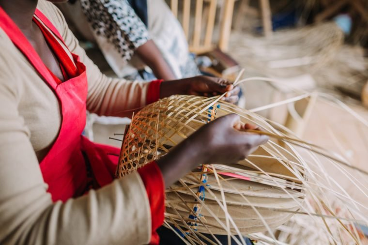 woman weaving a basket out of bamboo in Rwanda Africa