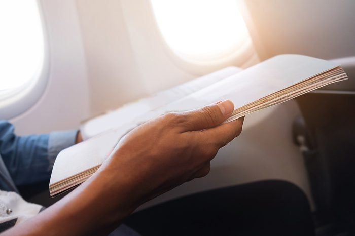happy traveler reading a magazine in an airplane,
