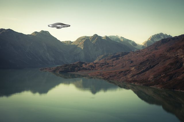 A UFO spaceship hovering over an alien landscape with water and mountains.