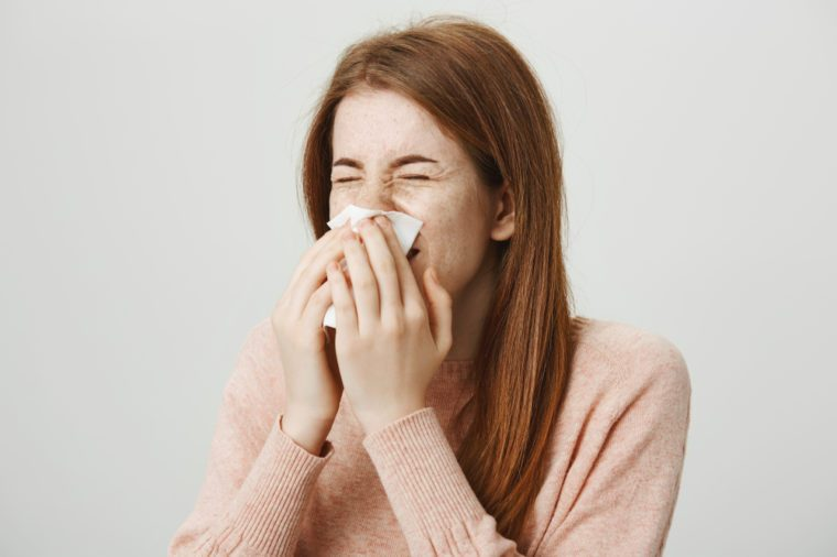 Close-up portrait of cute young ginger girl sneezing in napkin while standing against gray background. Woman has flu so she can not go to work today. Student crying while watching melodrama