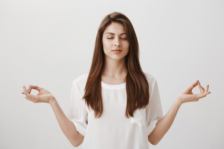 Let there be calm. Portrait of focused relaxed attractive female with closed eyes, happy smile, meditating with spread hands and zen gesture, being concentrated on yoga class, standing over gray wall