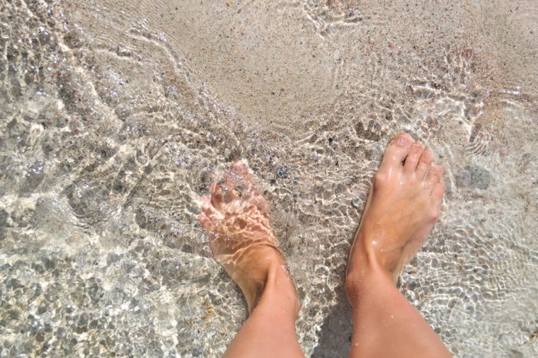 Feet in the water on the sand. Mediterranean sea, the island of Crete. Greece.