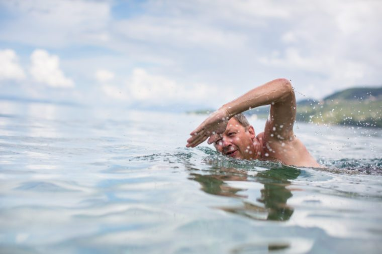Senior man swimming in the Sea/Ocean - enjoying active retirement, having fun, taking care of himself, staying fit