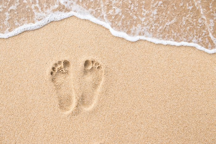 Footprint on beach in sand and wave.