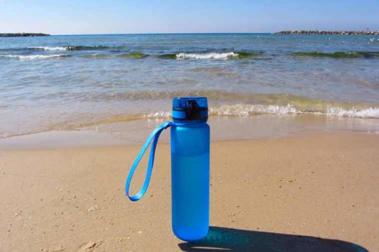 bottle with water against the sea