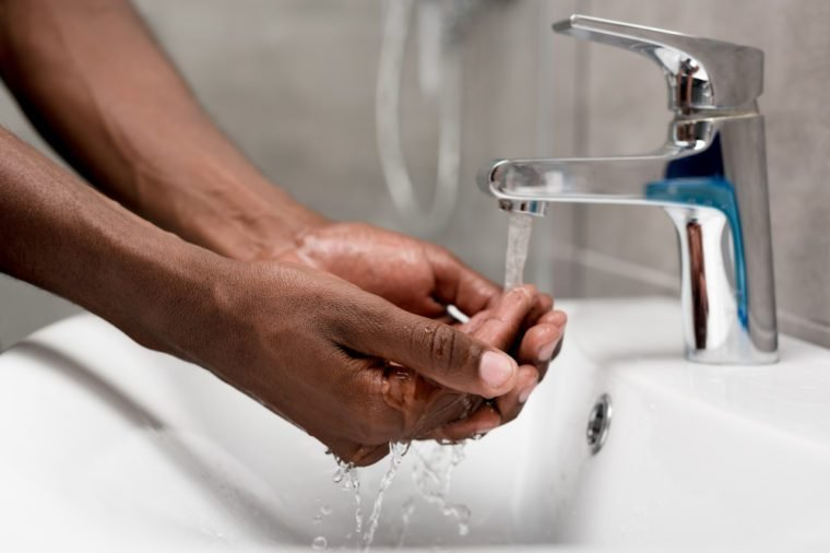 close-up partial view of african american man washing in bathroom
