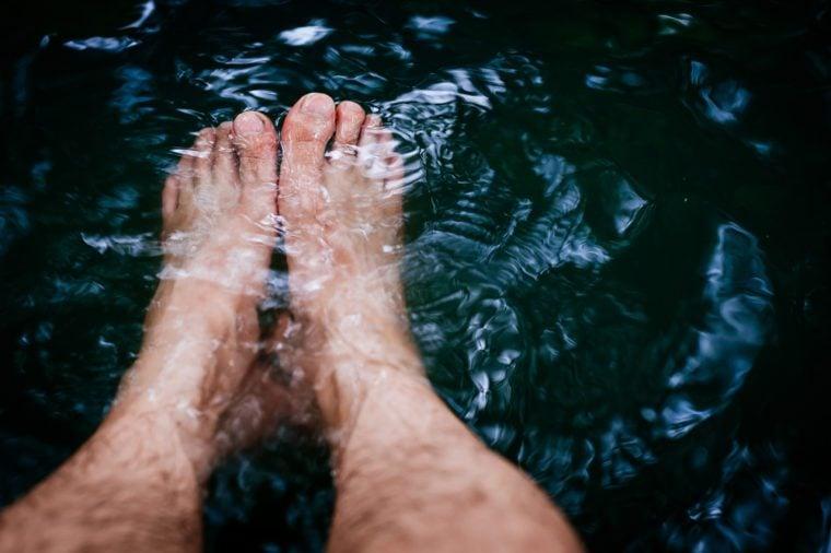 A man foot in the stream line of deep dark water